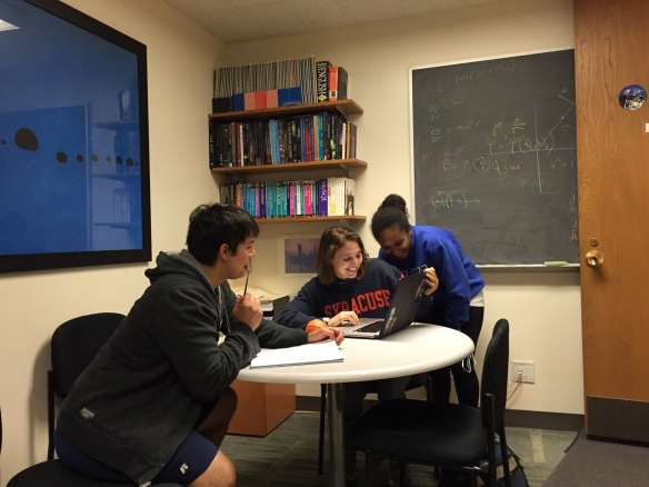 Samantha Usman (center) waits with student researchers Steven Reyes and Amber Lenon wait to see the closed-box results of Usman's analysis.